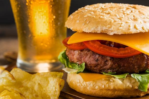 Bicchiere di birra con cheeseburger e patatine Foto Gratuite