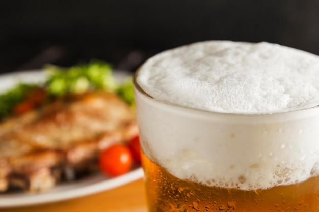 Bicchiere di birra con bistecca sfocati Foto Gratuite