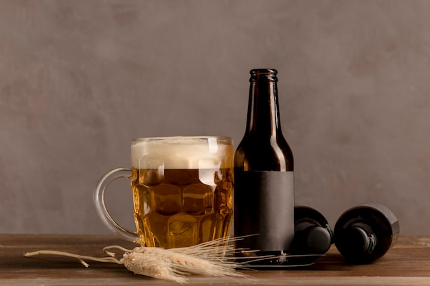 Glass of beer with foam and brown bottles of beer on wooden table Free Photo