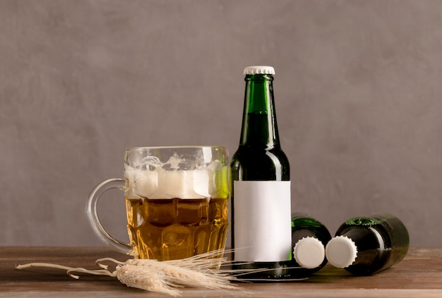 Glass of beer with foam and green bottles of beer on wooden table Free Photo