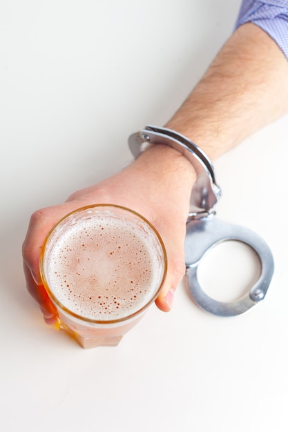 Glass of beer with handcuffs as symbol for alcohol abuse Premium Photo