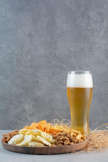 Un bicchiere di birra con frumento e patatine fritte sul fieno. Foto Gratuite