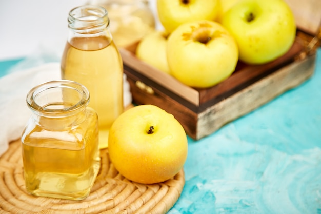 Glass bottle of apple organic vinegar on blue. Premium Photo