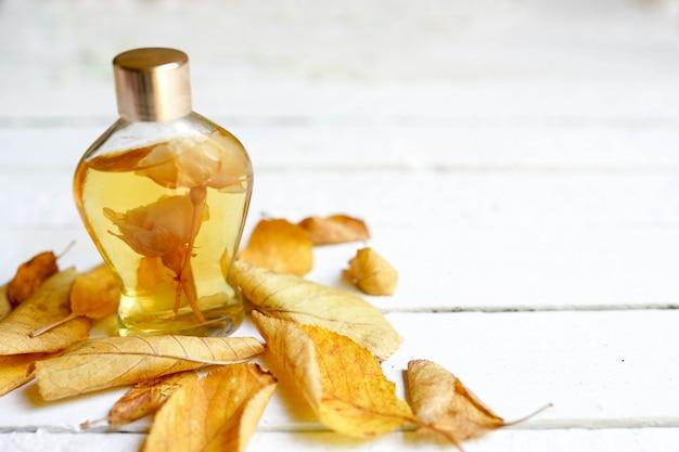 A glass bottle of female perfume with autumn yellow leaves. natural perfumery. autumn season. Premium Photo