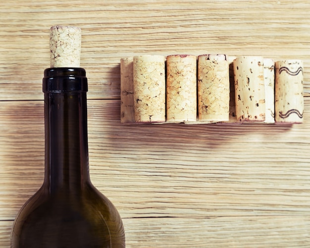 Glass bottle of red wine with corks. on old wooden table. top view. soft focus. toned photo. Premium Photo