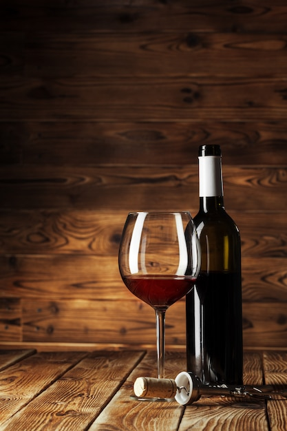 Glass and bottle with delicious red wine on table against wood Premium Photo