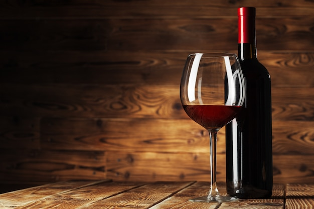 Glass and bottle with delicious red wine on table against wooden Premium Photo