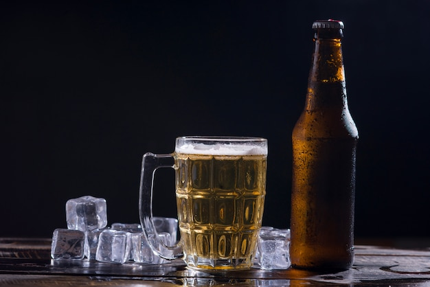 Glass bottles of beer with glass and ice on dark background Free Photo