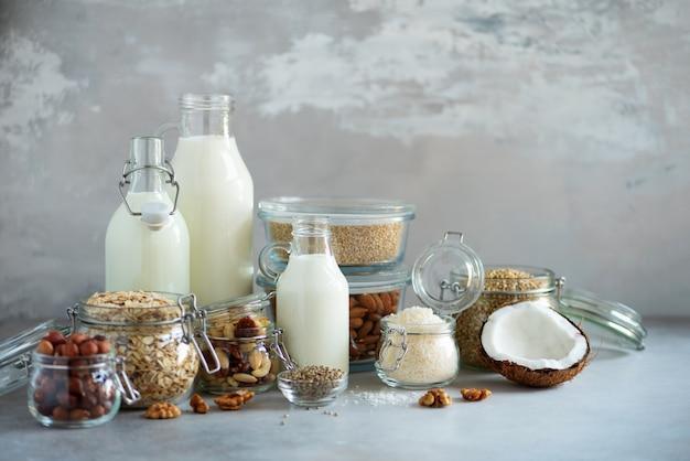 Glass bottles of vegan plant milk and almonds, nuts, coconut, hemp seed milk on grey concrete background. Premium Photo