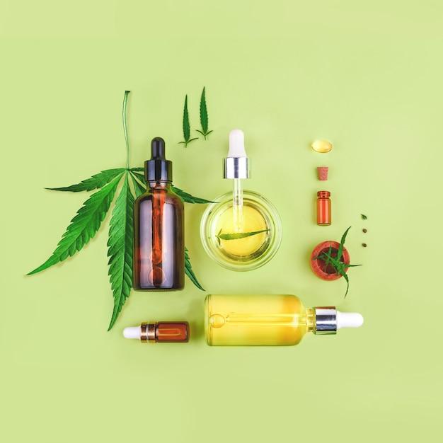 緑にcbdオイル、thcティンクチャー、麻の葉が入ったガラス瓶 Premium写真