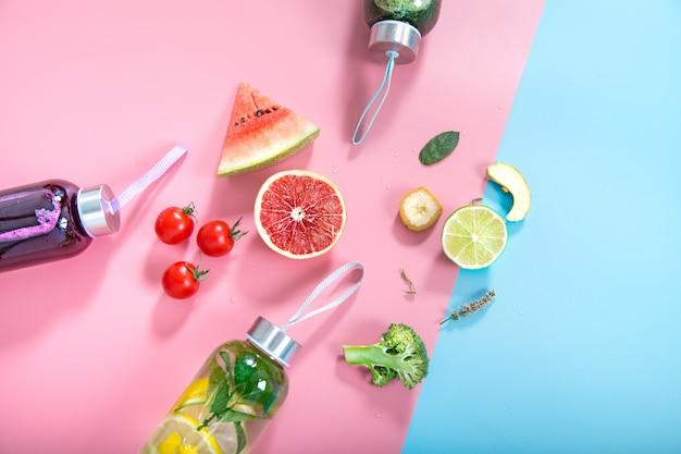 Стеклянные бутылки с натуральными напитками на цветной стене Бесплатные Фотографии