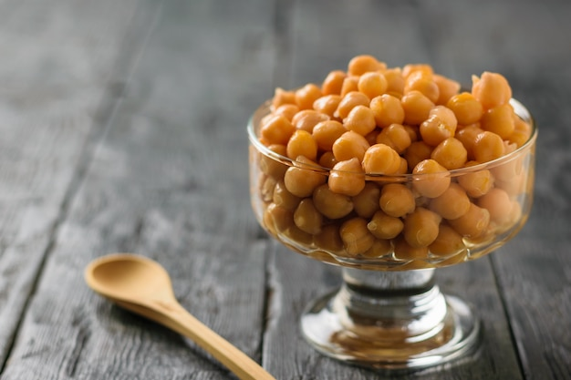 Glass bowl filled with boiled chickpeas with wooden spoon on a rustic table. vegetarian cuisine from legumes. Premium Photo