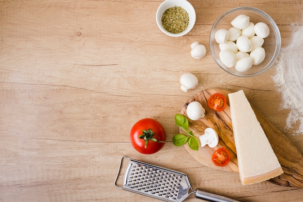 Glass bowl of mozzarella cheese; tomatoes; basil and cheese block with grater on desk Free Photo