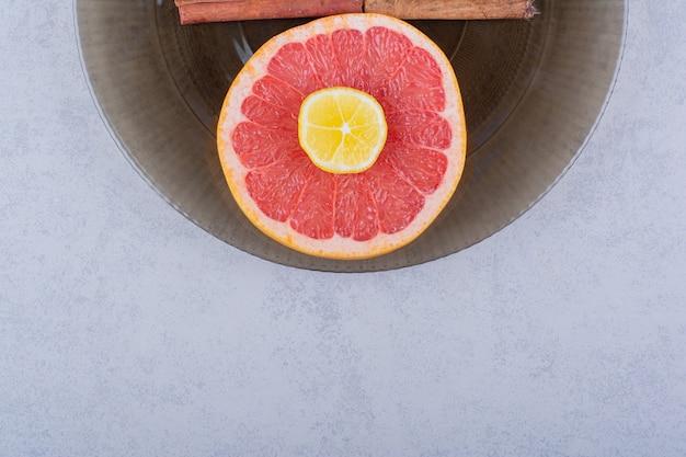 石のテーブルにレモンと新鮮なグレープフルーツスライスのガラスのボウル。 無料写真