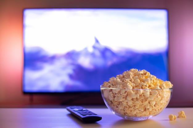 A glass bowl of popcorn and remote control. Premium Photo