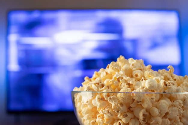 Glass bowl with popcorn and working tv. Premium Photo