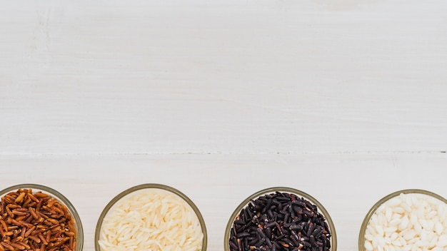 Glass bowl with variety of rice arranged at the bottom of background Free Photo
