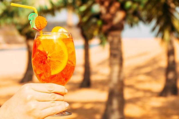 Glass of bright orange drink  in hand Free Photo
