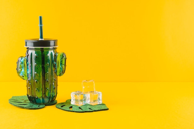 Glass cactus juice jar and crystal ice cubes on leaves coasters against yellow backdrop Free Photo