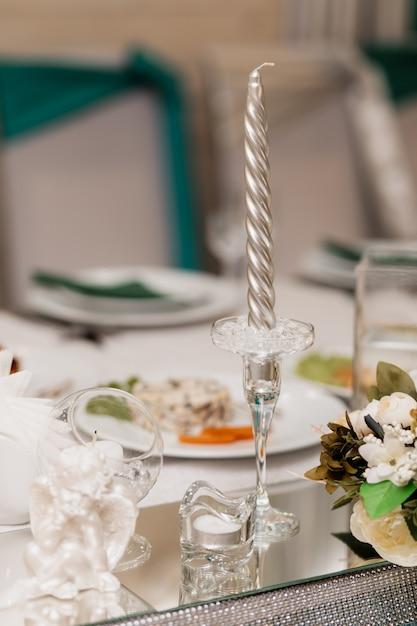 Стеклянный подсвечник с серебряной свечой и другие предметы декора на столе Бесплатные Фотографии