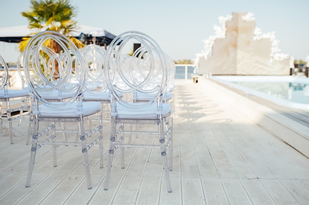 유리 의자는 아름다운 결혼식 나들이 행사에 나란히 서 있습니다. 프리미엄 사진