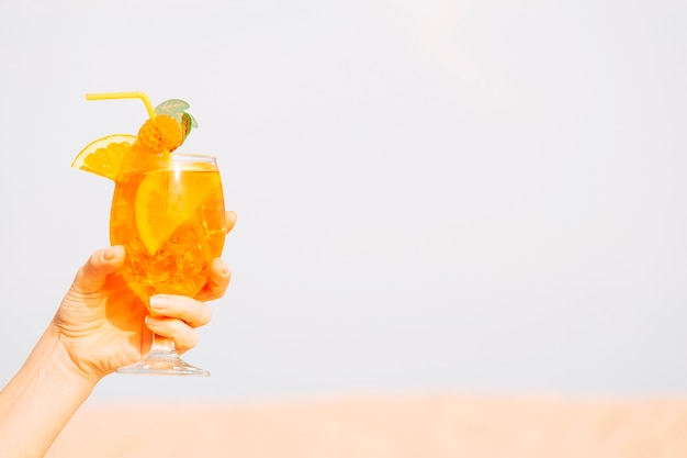 Glass of chilling orange drink  in hand Free Photo