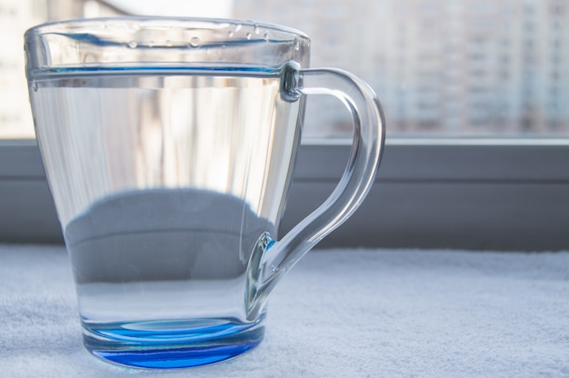 Glass of clean drinking water stands on the window on a sunny day Premium Photo