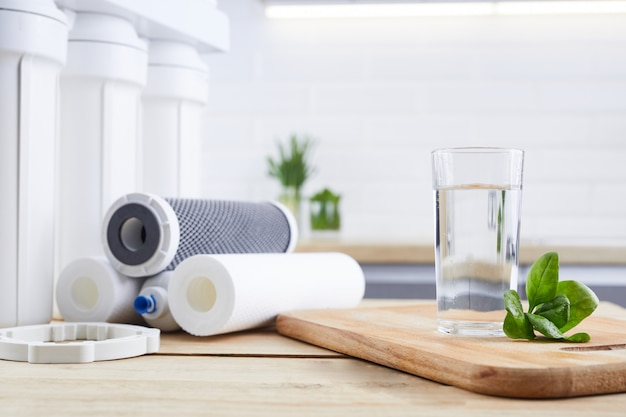 A glass of clean water with osmosis filter, green leaves and cartridges on wooden table in a kitchen interior Premium Photo