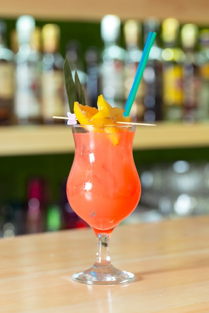 Glass of cocktail decorated with fruits at bar counter. Premium Photo