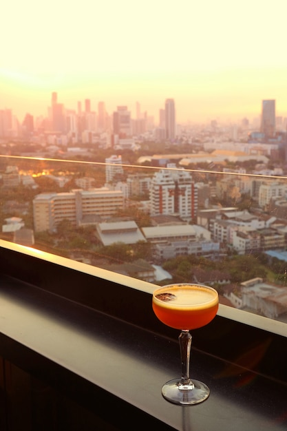 Glass of cocktail on the rooftop bar with aerial urban view in background. Premium Photo