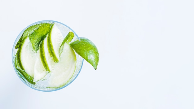 Glass of cocktail with slices of lime and peppermint Free Photo