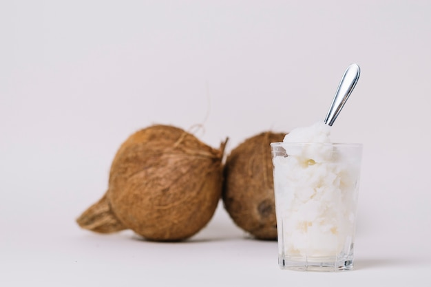 Glass of coconut oil with coconut nuts Free Photo