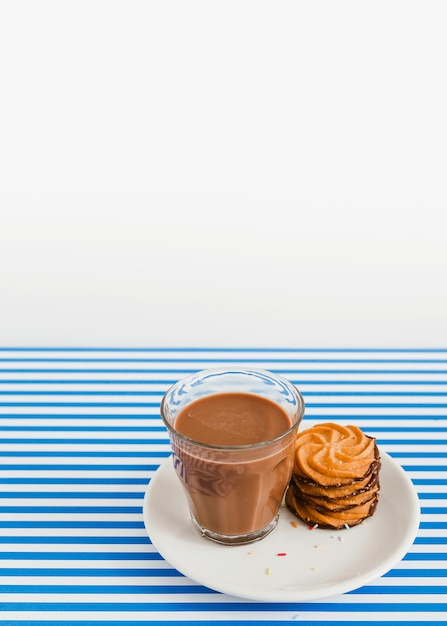 Glass of coffee and stack of cookies on plate over white and stripes background Free Photo