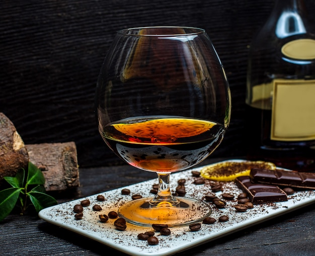Glass of cognac and chocolate bars Free Photo