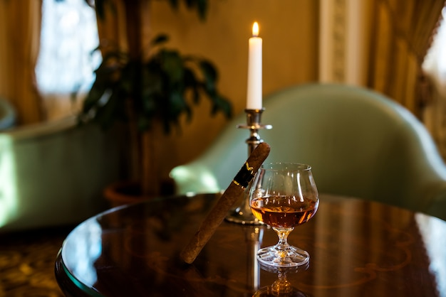 A glass of cognac and a cigar on the table. Premium Photo