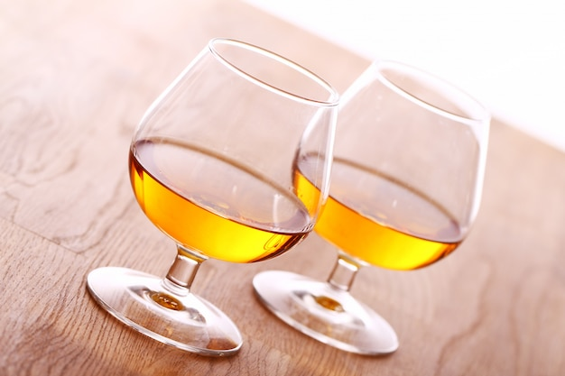 Glass of cognac over wooden surface Free Photo