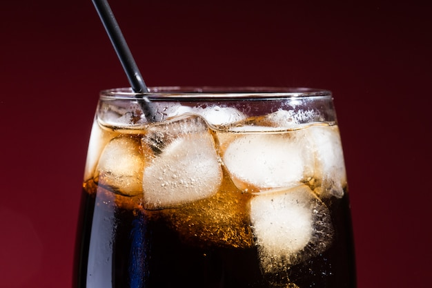 A glass of cola beverage with a salt, on a red , Premium Photo