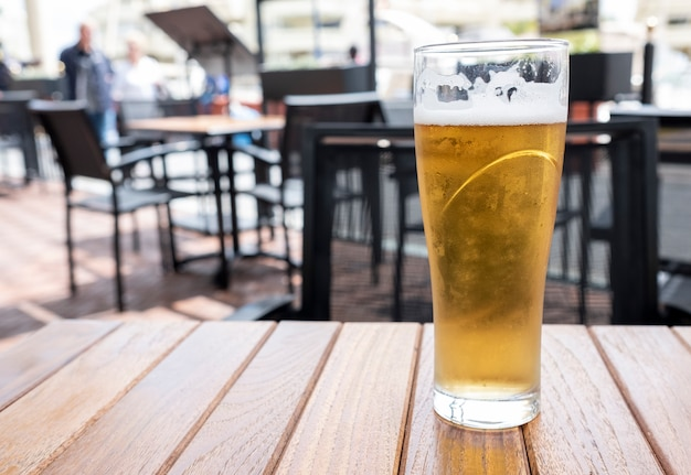 Glass of cold beer with foam on a wooden table Premium Photo