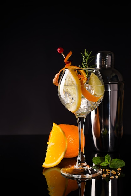 Glass of a cold cocktail drink with white wine served with brown sugar, orange and shaker Premium Photo