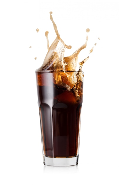 A glass of cold cola with a splash of ice cubes Premium Photo