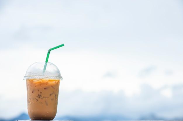 Glass of cold espresso coffee background blurry views sky. Premium Photo