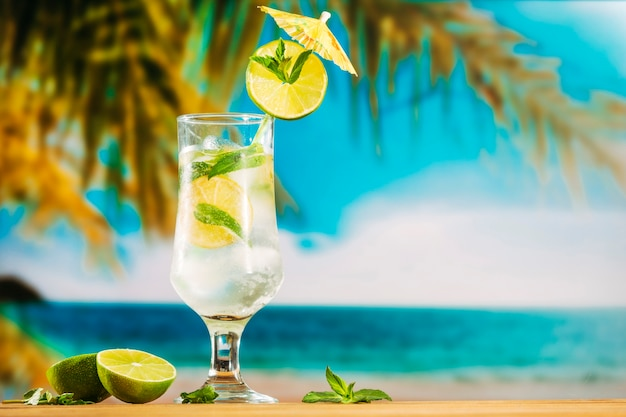 Glass of cold lime water with umbrella Free Photo