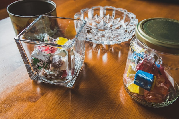 Glass containers filled with candies on wooden table Premium Photo