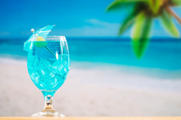 Glass of cooling blue drink decorated with olive and umbrella Free Photo