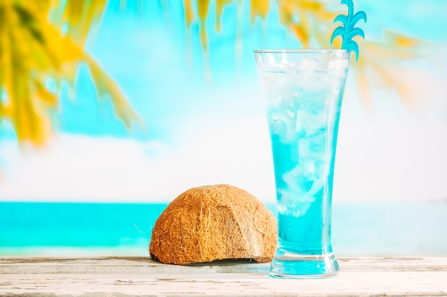 Glass of cooling blue drink and inverted coconut shell Free Photo