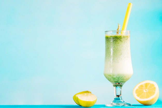 Glass of creamy green smoothie and sliced citrus Free Photo