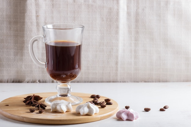 Glass cup of coffee with meringues on a wooden board on a white background. Premium Photo