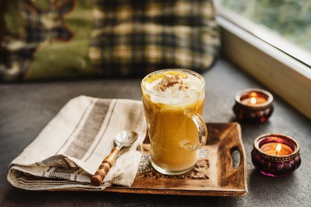 A glass cup of pumpkin spice latte next to a window Premium Photo