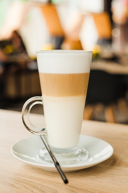 Glass cup with hot latte on wooden table at cafeteria Free Photo