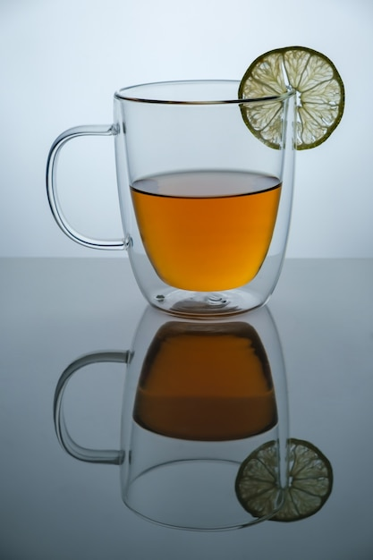 검은 거울 표면, 스튜디오 광고 샷, 복사 공간에 뜨거운 차와 레몬 유리 컵 프리미엄 사진